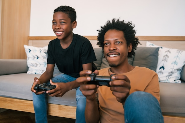 Portrait of happy african american father and son sitting in sofa couch and playing console video games together at home