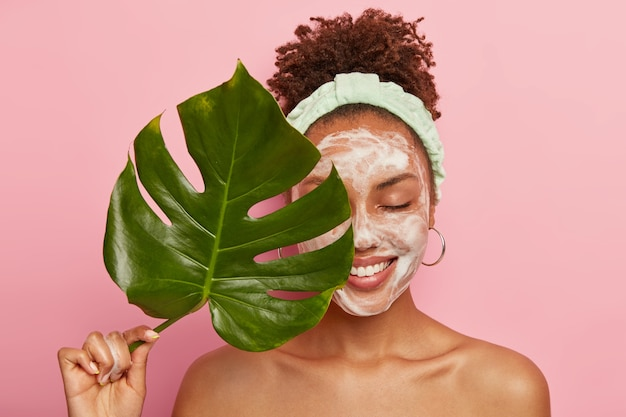 Portrait of happy african american woman covers half of face with green leaf, cleans face, washes with bubble soap, stands topless, cares aboout her beauty and body