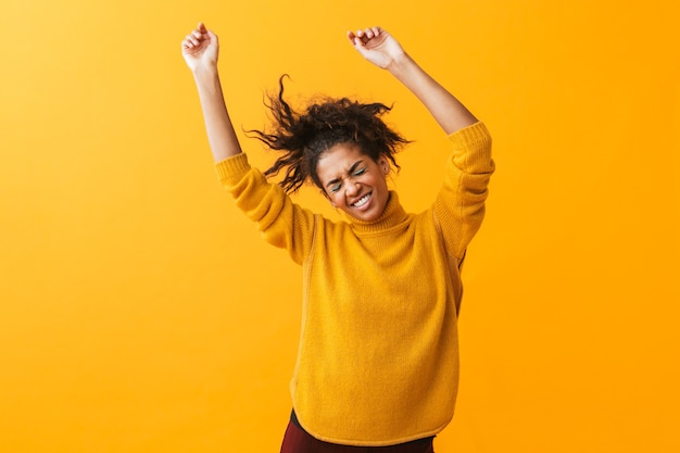 Portrait of happy african american woman with afro hairstyle rejoicing and dancing, isolated