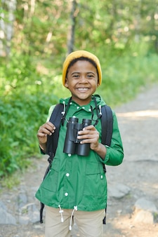 Portrait of happy african boy holding binoculars and smiling at camera in the forest