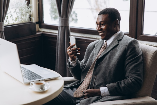 Portrait of happy african businessman using phone while working on laptop in a restaurant.