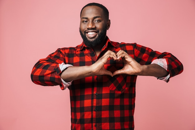 Portrait of a happy african man wearing plaid shirt standing isolated over pink wall