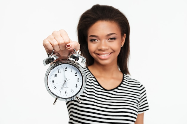 Portrait of a happy african teen woman showing alarm clock