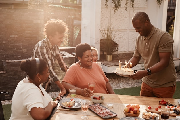 Portrait of happy africanamerican family celebrating grandmothers birthday outdoors lit by sunlight ...