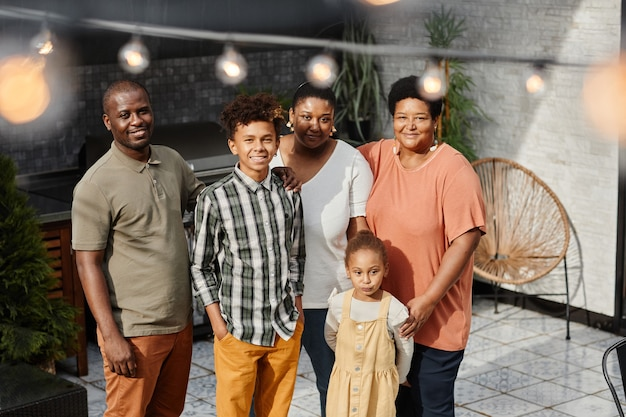 Portrait of happy africanamerican family looking at camera while posing at terrace outdoors multigen...