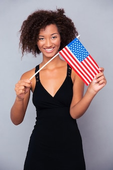 Portrait of a happy afro american woman holding usa flag over gray wall and looking at front