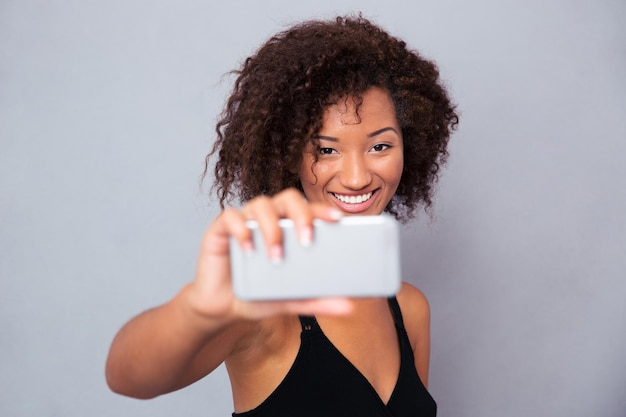 Portrait of a happy afro american woman making selfie photo on smartphone over gray wall