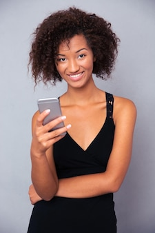 Portrait of a happy afro american woman using smartphone over gray wall
