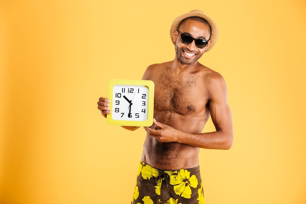 Portrait of a happy afro man in swimwear holding wall clock isolated on a orange wall
