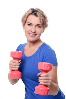 Portrait of happy aged sportswoman with dumbbells