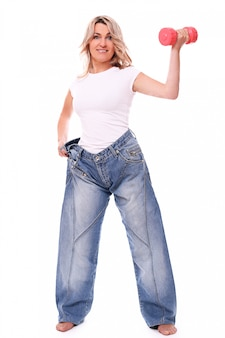 Portrait of happy aged woman wearing big jeans and dumbbell