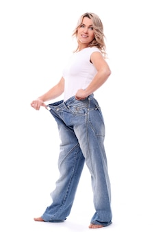 Portrait of happy aged woman with big jeans
