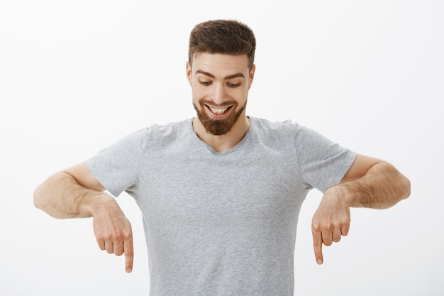Portrait of happy and amazed good-looking masculine male with perfect hairstyle and beard looking and pointing down with delight and curiosity enjoying watching downwards at interesting copy space