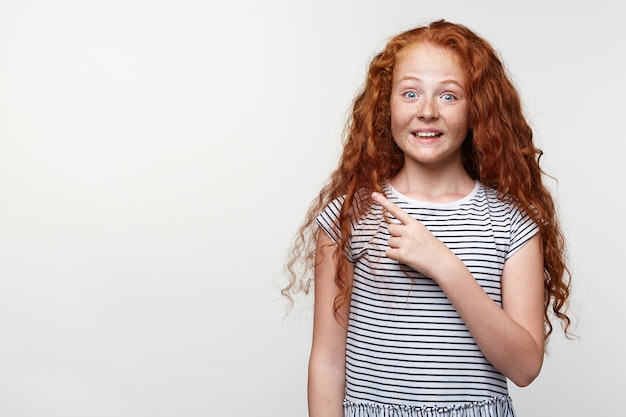 Portrait of happy amazed little girl with ginger hair and freckles, wants to draw you attention to the copy space on the left side and points with fingers, stands over white wall and broadly smiling.