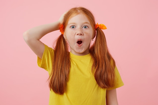 Portrait of happy amazed petite freckles red-haired girl with two tails, wears in yellow t-shirt, stands over pink background with wide open mouth.