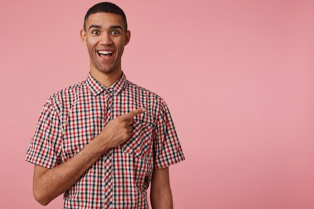 Ritratto di felice stupito giovane attraente dalla pelle scura ragazzo in camicia a scacchi, bocca spalancata e occhi, si leva in piedi su sfondo rosa vuole attirare la vostra attenzione sullo spazio della copia a destra.