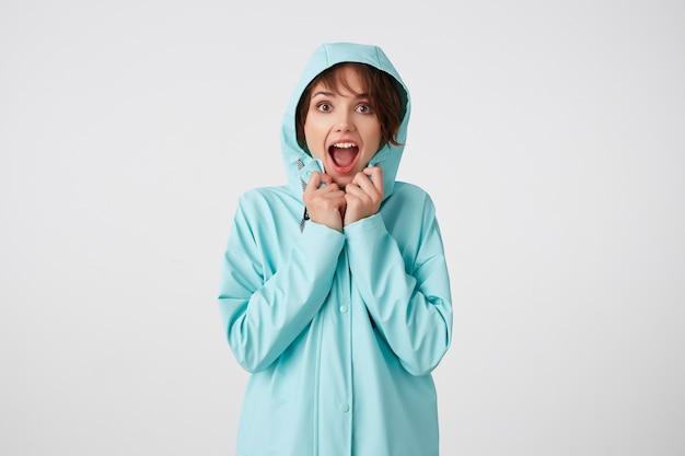 Ritratto di giovane donna carina stupita felice in cappotto di pioggia blu, con un cappuccio in testa, guarda la telecamera con espressioni di sorpresa, si trova sopra il muro bianco.