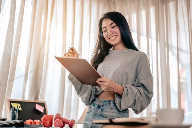 ノートブックを書いて、ホームオフィスで働く幸せで笑顔の女性の肖像画自宅で仕事