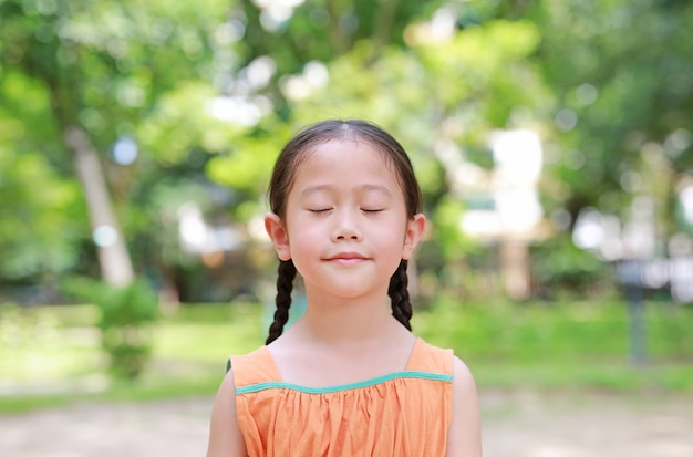 Portrait of happy asian child close their eyes in garden with breathe fresh air from nature. close up kid girl relax in green park for good health.
