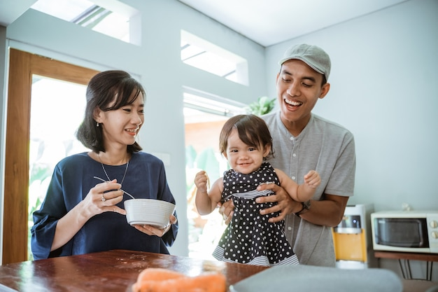 Portrait of happy asian father mother and daughter cooking together in modern kitchen