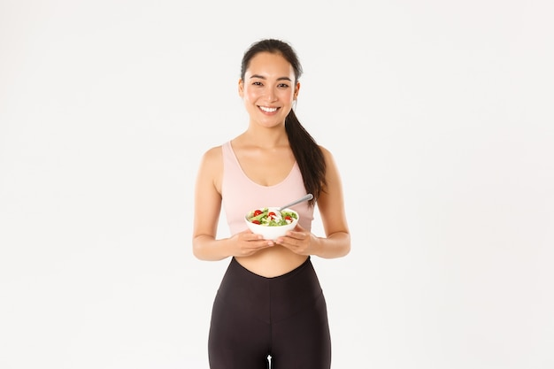 Portrait happy asian female athlete, fitness girl smiling while eating healthy salad, taking care or body weight on diet, exercise to gain perfect body.