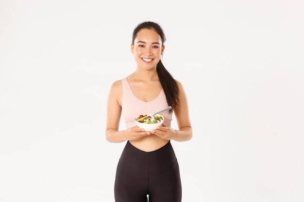 세로 행복 아시아 여성 운동 선수, 건강 샐러드를 먹는 동안 웃 고 피트니스 소녀, 다이어트에 돌보는 또는 체중, 완벽한 몸을 얻기 위해 운동.