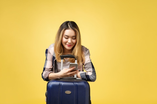 Portrait of happy asian female traveler with suitcase and looking at cellphone