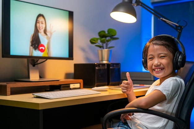 Portrait of happy asian girl using video teleconference for online studying with her teacher at home. distance learning, online learning, technology or remote connection concepts