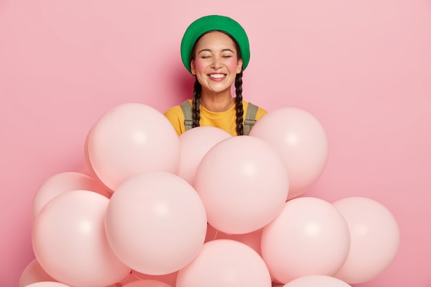 Portrait of happy asian lady in green hat, has two braids, rouge cheeks, expresses positive emotions stands near many one colored balloons
