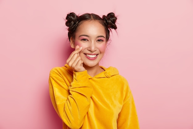 Portrait of happy asian lady with pleasant smile on face, makes like sign, shapes heart with fingers, wears yellow sweatshirt