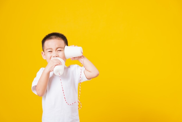 Portrait happy asian little child boy smile playing paper can telephone