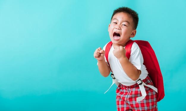 Portrait of happy asian little child boy in uniform smile raise hands up glad when go back to school