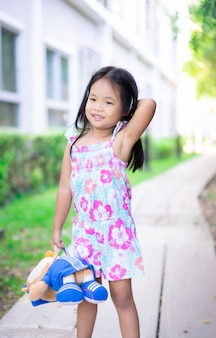 Portrait of happy asian little girl with doll standing on footpath in the park