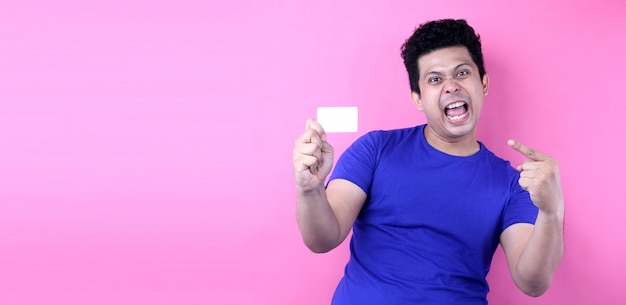 Portrait of happy asian man holding credit card isolated on pink wall.