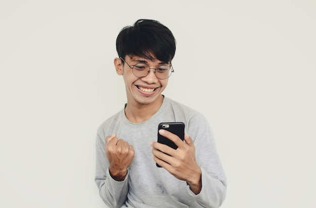 Portrait of a happy asian man looking at a smartphone
