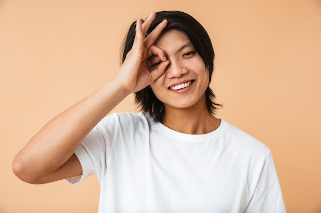 Portrait of a happy asian man wearing t-shirt standing isolated over beige wall, showing ok