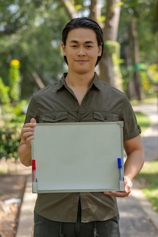 Portrait of happy asian young man standing in the park and showing blank signboard