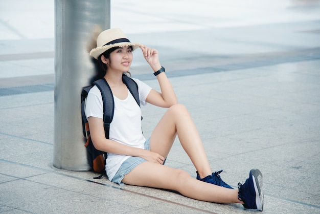Portrait of a happy asian young woman sitting on the city