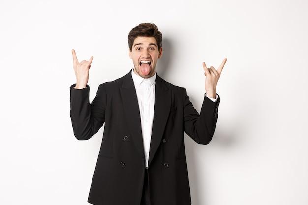 Ritratto di felice ragazzo attraente che si diverte alla festa, indossando un abito nero, mostrando il segno e la lingua rock-n-roll, in piedi eccitato su sfondo bianco