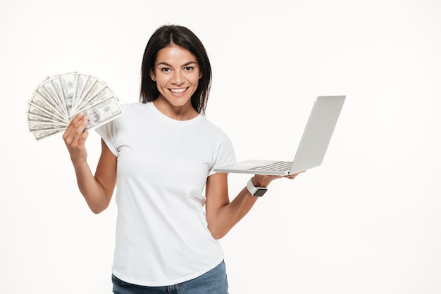 Portrait of a happy attractive woman holding laptop computer