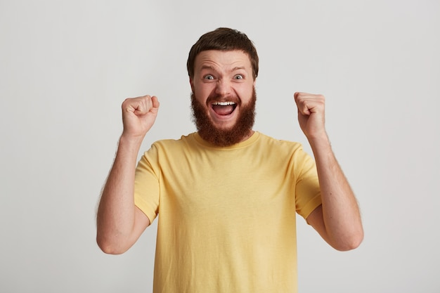 Portrait of happy attractive young man hipster with beard wears t shirt looks confident and excited