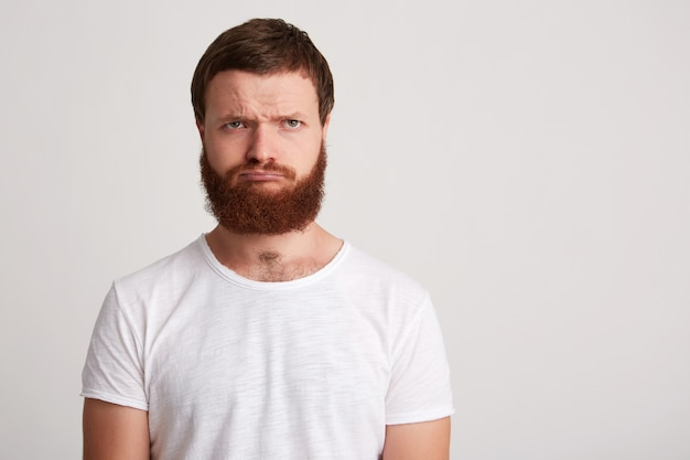 Ritratto di felice attraente giovane uomo hipster con barba indossa la maglietta sembra fiducioso