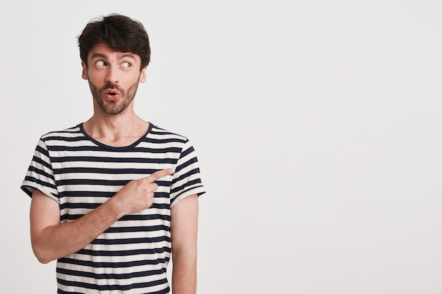 Portrait of happy attractive young man with bristle wears striped t shirt feels excited and smiling isolated on white