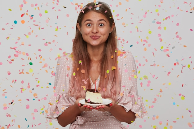 Ritratto di felice attraente giovane donna con lunghi capelli tinti di rosa pastello indossa un abito rosa a pois e mangia la torta