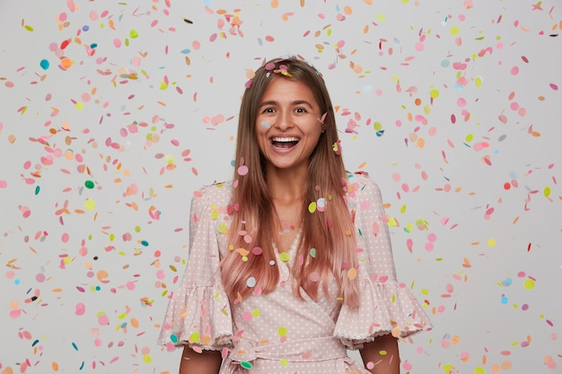 Portrait of happy attractive young woman with long dyed pastel pink hair wears polka dot pink dress and having party