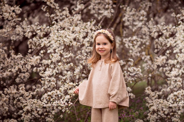 Portrait of a happy baby girl on a background of flowering trees.