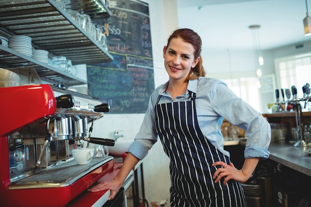 Portrait of happy barista standing at cafe