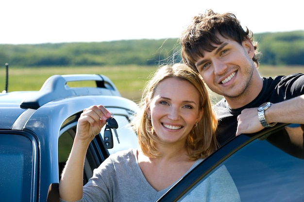 Portrait of happy bautiful couple showingh the keys standing near the car
