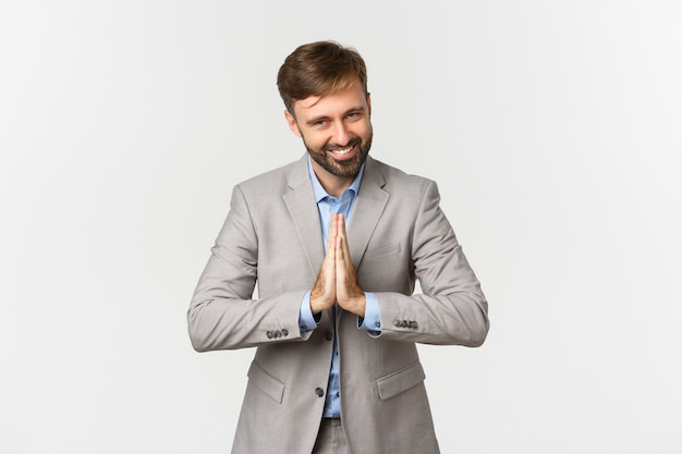 Portrait of happy bearded businessman in grey suit, thanking for something