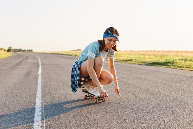 Ritratto di felice bella donna dai capelli scuri che indossa abbigliamento casual e fascia per capelli surf seduto su skateboard, divertirsi all'aperto da solo, sano stile di vita attivo.